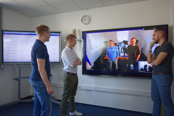 People standing in front of a screen during a video conference in a distributed team