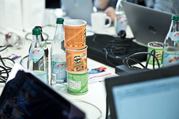 Getränke und Snacks stehen auf Schreibtischen zwischen Laptops