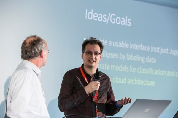 Personen halten einen Vortrag, im Hintergrund ist eine Leinwand zu sehen