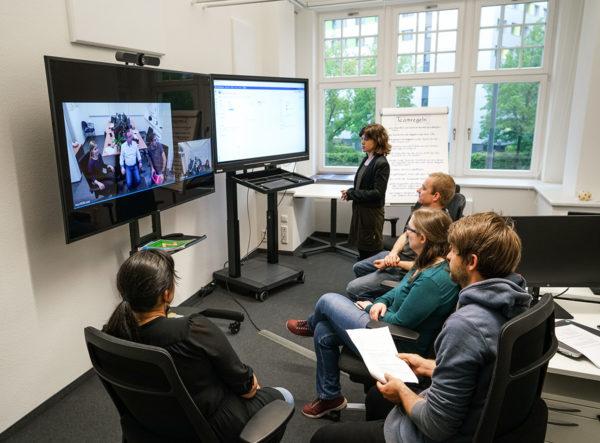 Mehrere Personen sitzen vor zwei großen Monitoren, auf denen einerseits ein weiteres Team von Personen per Videokonferenz zugeschaltet ist sowie andererseits eine Aufgabenliste zu sehen ist.