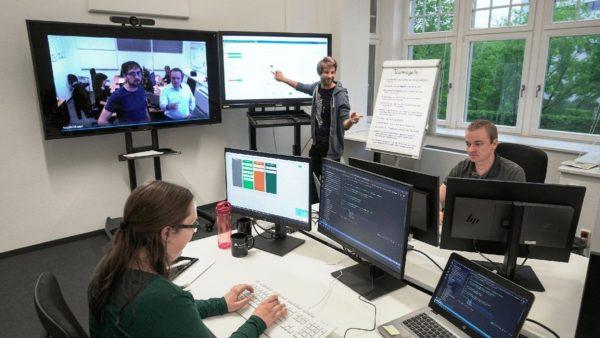 Ein Team arbeitet verteilt über zwei Standorte zusammen und ist per Videokonferenz zusammengeschaltet.