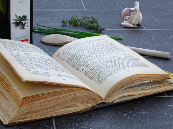 Altes Buch mit Rezepten liegt neben Koch- und Küchenutensilien