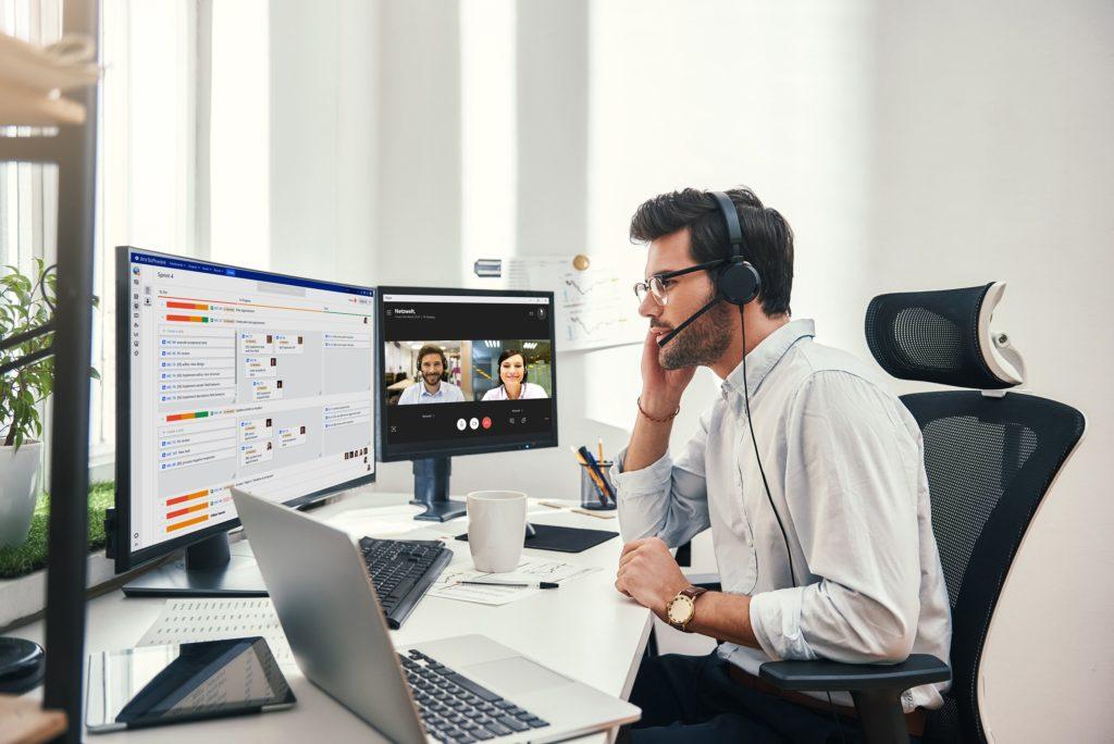 Person sitzt vor Laptop und mehreren Monitoren während einer Videokonferenz und nutzt das Tool ETEOboard für verteilte Zusammenarbeit