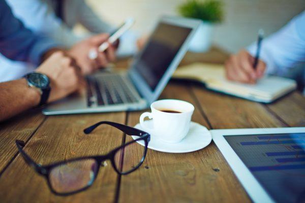 Tasse Kaffee und Brille im Büro-Arbeitsumfeld