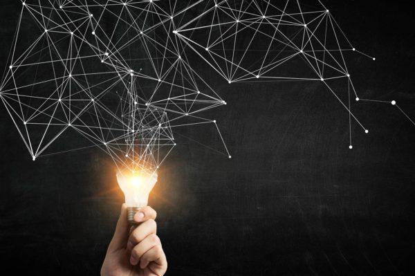 Hand, die eine Glühbirne hält, aus der untereinander vernetzte Punkte aufsteigen