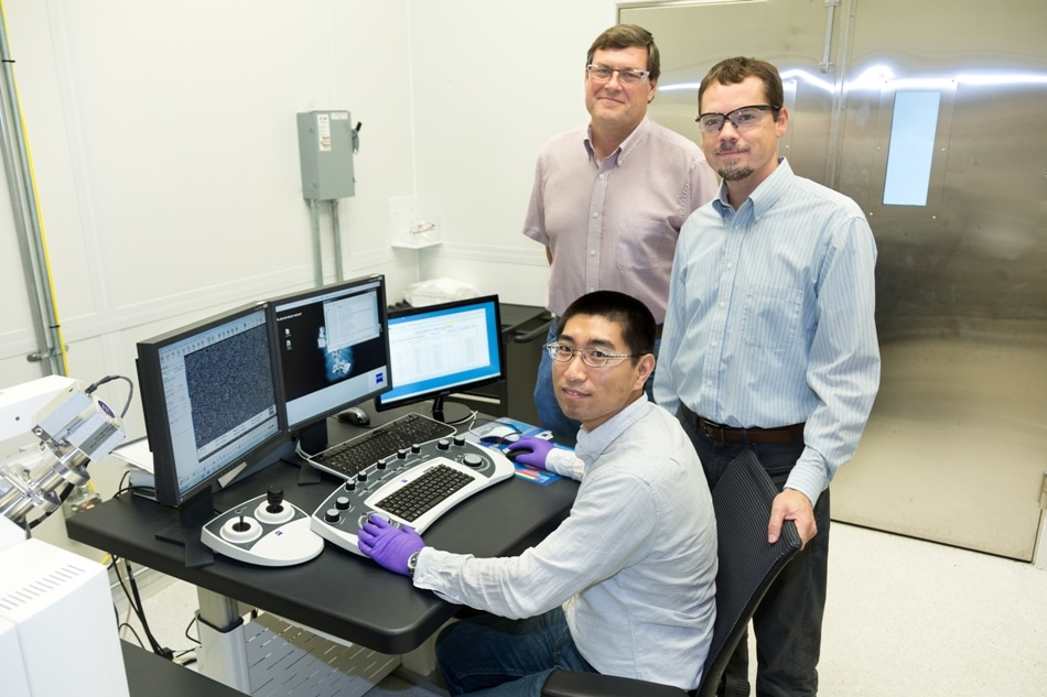 ORNL's Yang Song (seated), Dale Hensley (standing left) and Adam Rondinone examine a carbon nanospike sample with a ZEISS scanning electron microscope. (CREDIT: ORNL)