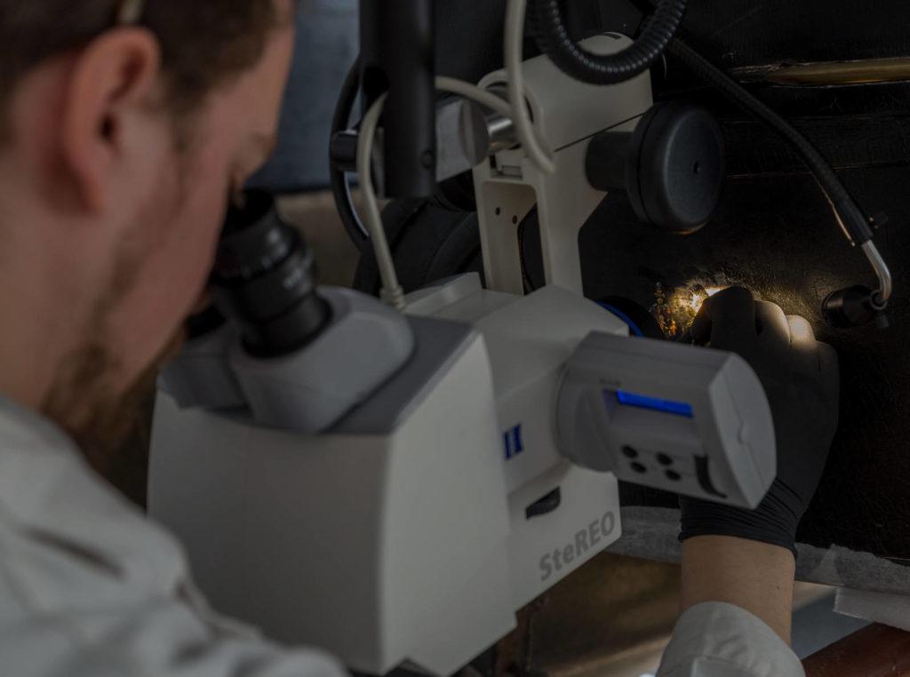 Matthias Manzini using a ZEISS stereo microscope.