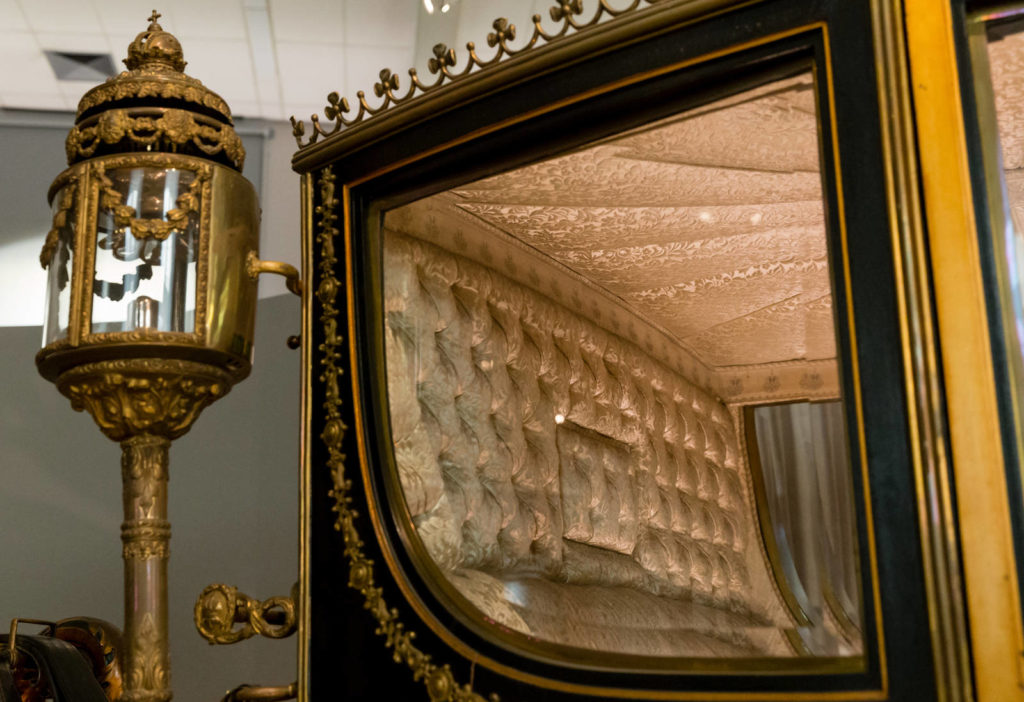 Gilded wooden structures, glass windows, padded interiors, embroideries, metal traction elements, paintings on the wooden elements: a carriage represents the interaction of a wide variety of materials.