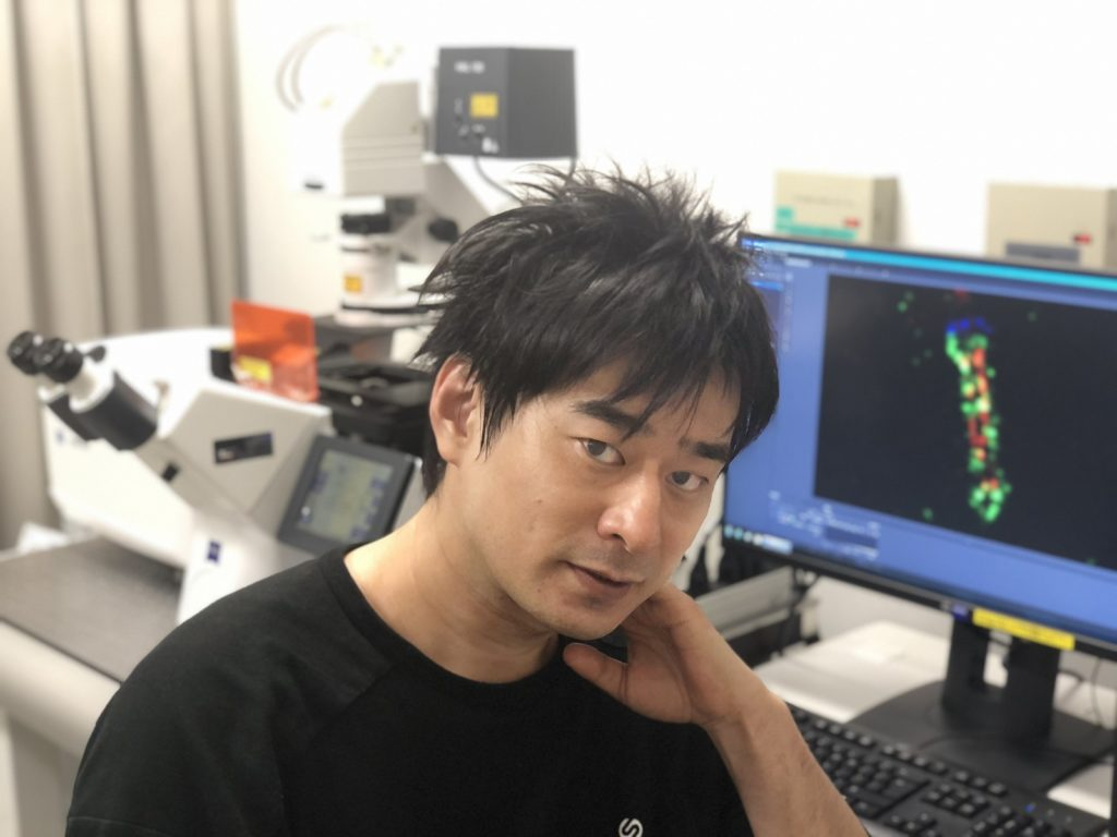 Dr. Shuhei Chiba. The monitor shows a primary cilium in a post-expansion sample.