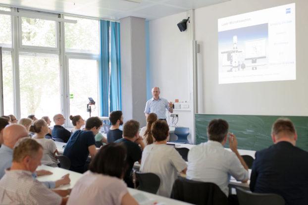 Dr. Ulrich Sauer (ZEISS) stellt dem interessierten Auditorium ZEISS PALM MicroBeam vor. Foto: Elvira Eberhardt / Uni Ulm