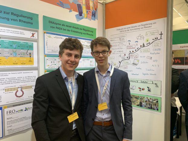 Die Biologie-Bundessieger von Jugend forscht 2019 Tobias Stadelmann (19) und Leon Stadelmann (17) aus Baden-Württemberg vor ihrem Forschungsposter.