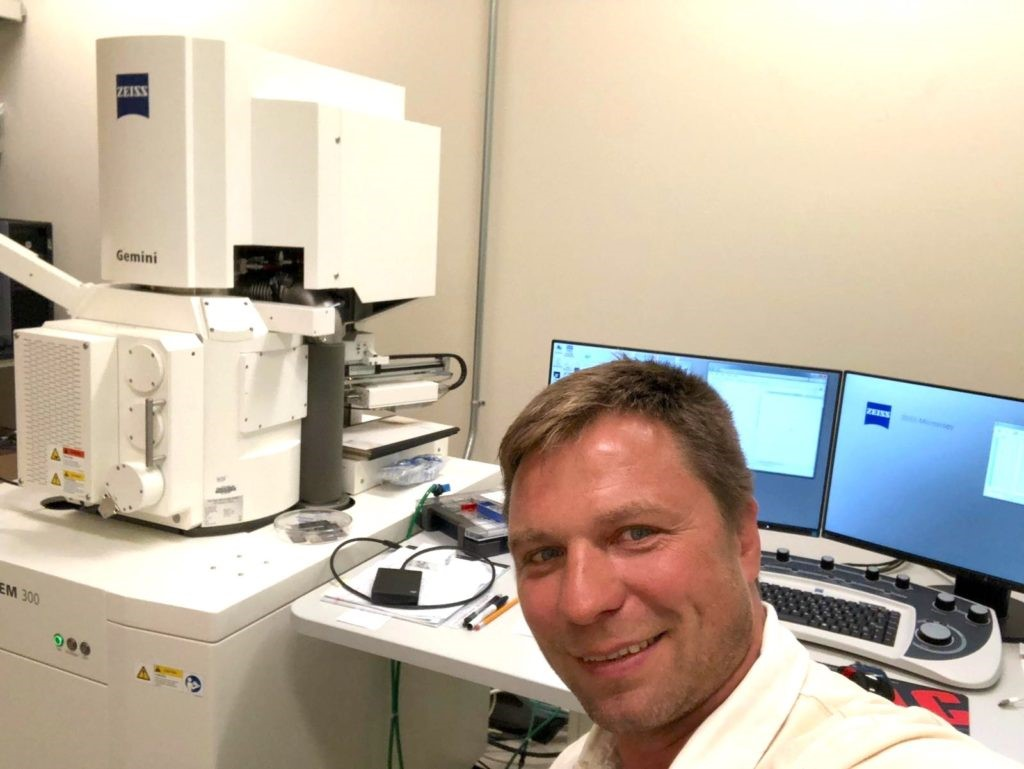 a man taking an image in front of the two minitors and a microscope