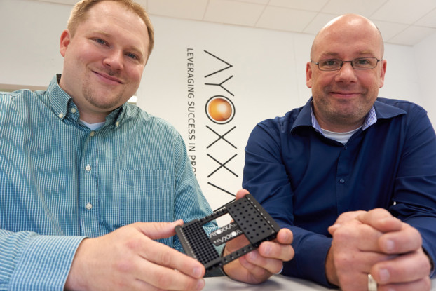 Dr. Lars Röglin (left), Senior Scientist Biochemistry at AYOXXA, with the platform for the biochip in his hand, and Dr. Bodo Borm from the ZEISS Democenter in Köln.