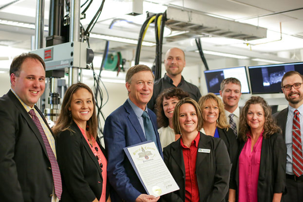 ADAPT team members celebrate the Governor's proclamation, naming October Colorado Manufacturing Month. Left to right: Aaron Stebner, Katie Woslager, Governor John Hickenlooper, Brandan Kappes, Mickele Bragg, Sumer Sorensen-Bain, Heidi Hostetter, Craig Brice, Alicia Svaldi and Douglas Van Bossuyt.