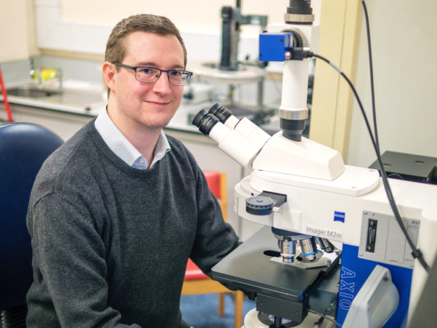 Dr Tom Harvey at his lab at University of Leicester with ZEISS Axio Imager microscope. Credit: Dr Tom Harvey/University of Leicester